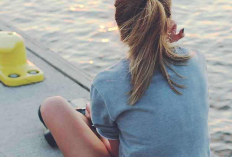teenager sitting by water